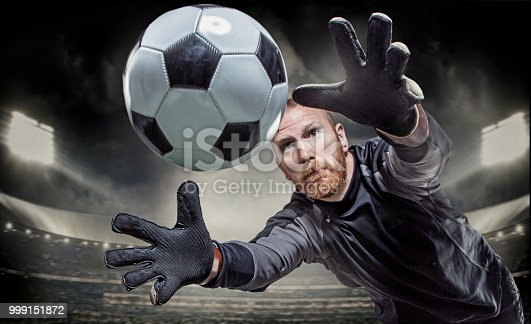istock Bearded Aggressive Redhead Adult Man Goalkeeper Saving a football in a floodlit soccer stadium 999151872