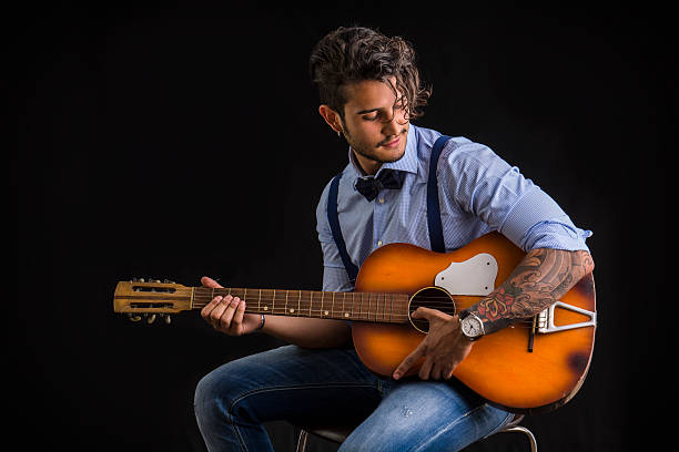 bearded and tattooed man with hairstyle playing guitar - tattoo schleife stock-fotos und bilder