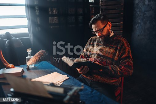 655113470 istock photo Bearded author in glasses reading a book 655113254