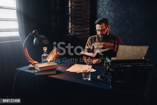 655113470 istock photo Bearded author in glasses reading a book 658122458