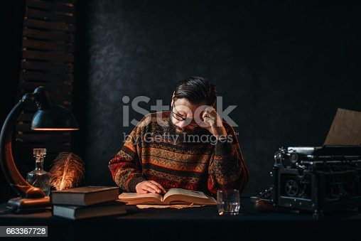 655113470 istock photo Bearded author in glasses reading a book 663367728