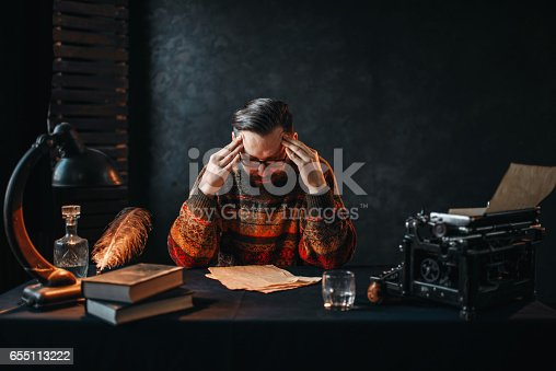 655113470 istock photo Bearded author in glasses reading his work 655113222