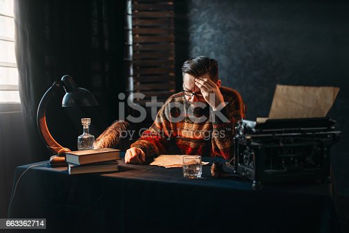 655113470 istock photo Bearded author in glasses reading his work 663362714