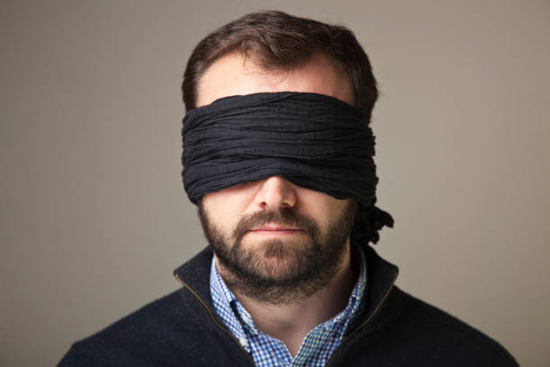 Bearded blindfolded man in a black jacket and blue shirt stock photo