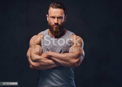 Portrait of brutal bearded bodybuilder with crossed arms dressed in a sleeveless shirt isolated on grey background.