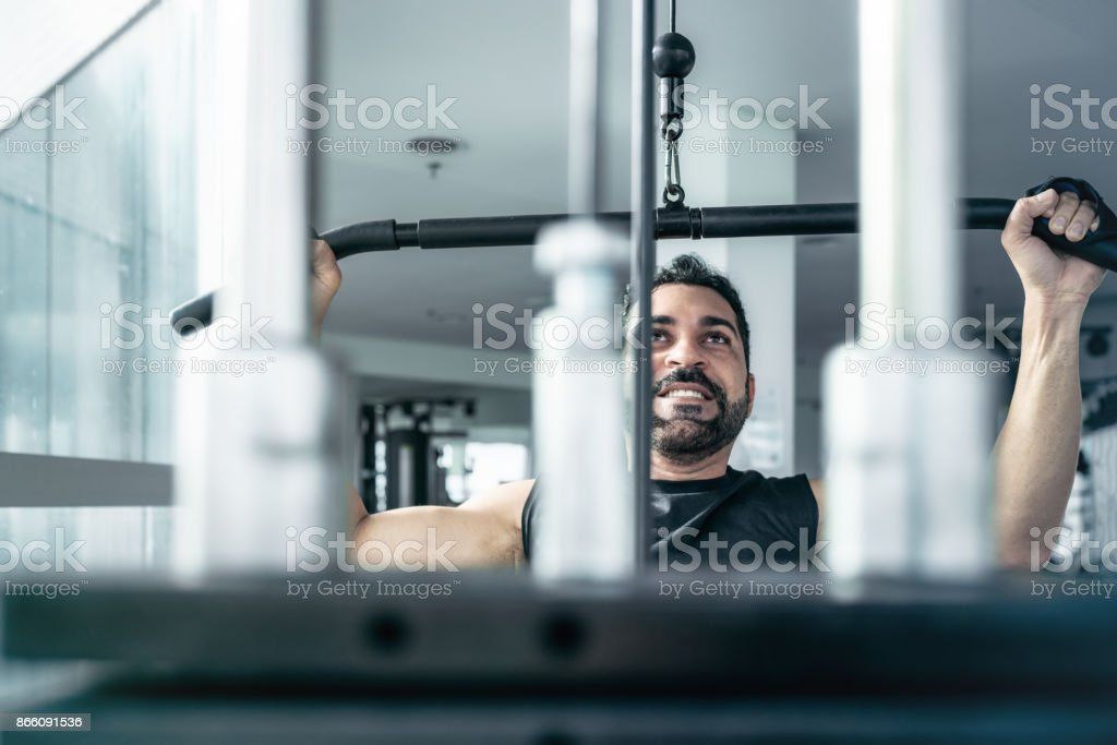 bearded brazilian athlete pulling weitght at exercise machine stock photo