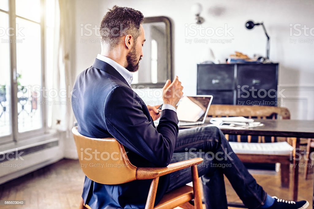 bearded business man looking at mobile in home office stock photo