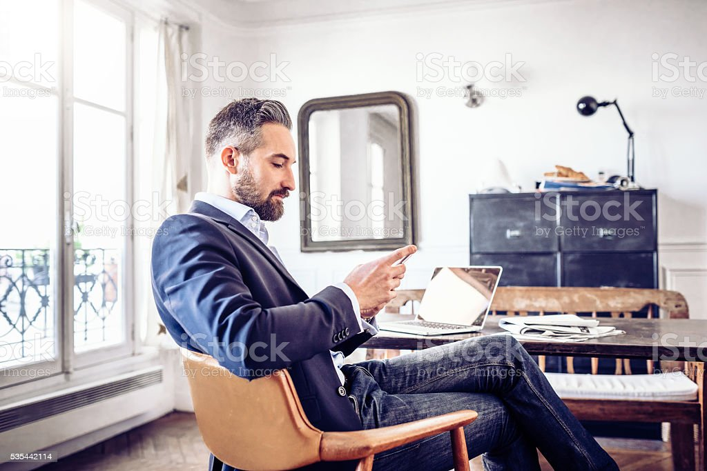 bearded business man reading on mobile in home office stock photo