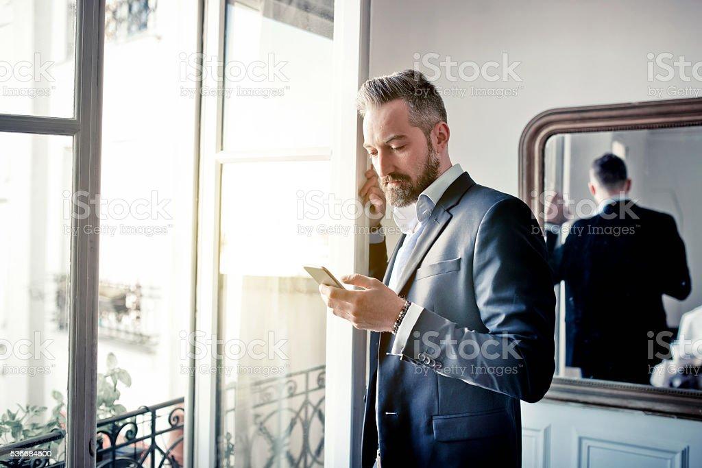 Barbu homme d'affaires lecture sur un smartphone à ouvrir la fenêtre - Photo