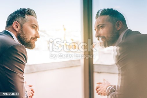istock bearded business man reflecting himself in window glass 536684690