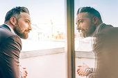bearded business man reflecting himself in window glass