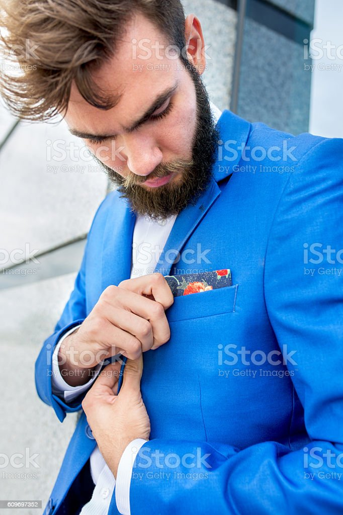 Bearded businessman adjusting handkerchief on suit. stock photo
