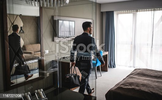 Young bearded executive in businesswear entering modern naturally lit hotel room with bag for a short stay.