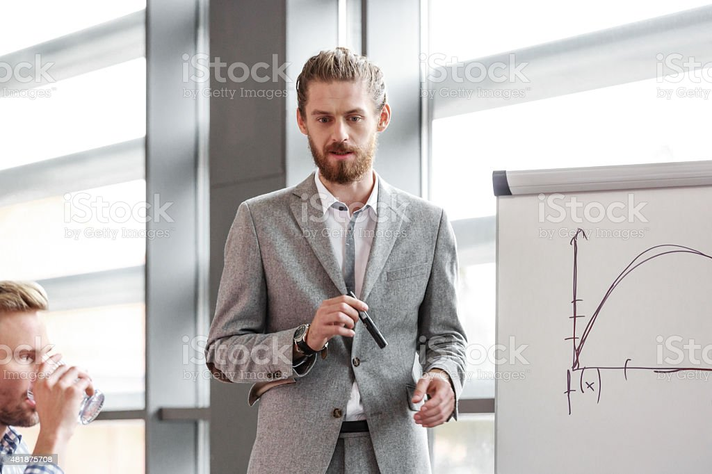 Bearded businessman giving presentation Bearded man wearing grey suit standing next to flipchart in the meeting room in an office and giving presentation.  2015 Stock Photo