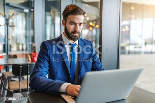 istock Bearded businessman in formal wear with serious facial expression using laptop while sitting in cafeteria next to window. 1128536214