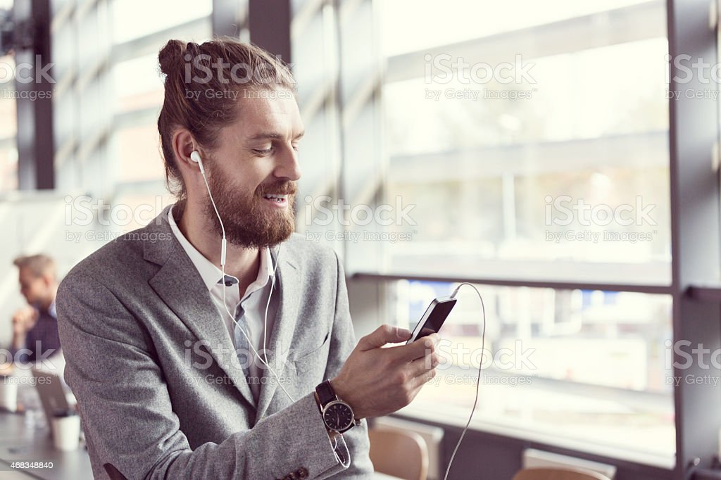 Bearded businessman listening to music using phone royalty-free stock photo