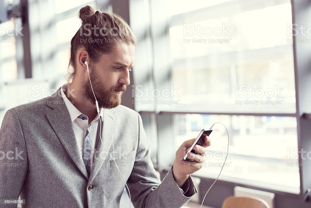 Bearded businessman listening to music using phone Portrait of bearded businessman wearing grey suit nad white headphone listening to music using smart phone in the office. 2015 Stock Photo