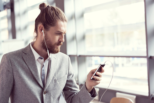 Bearded Businessman Listening To Music Using Phone Stock Photo - Download Image Now