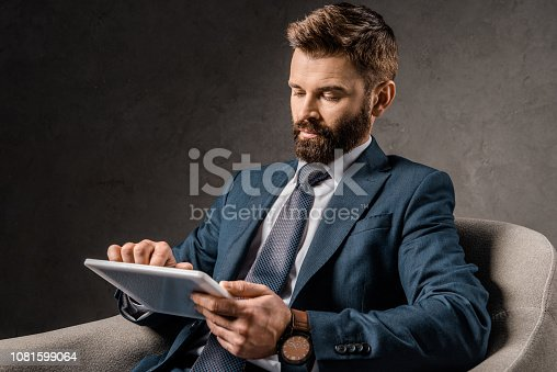 1081599130 istock photo bearded businessman using digital device while sitting in armchair 1081599064
