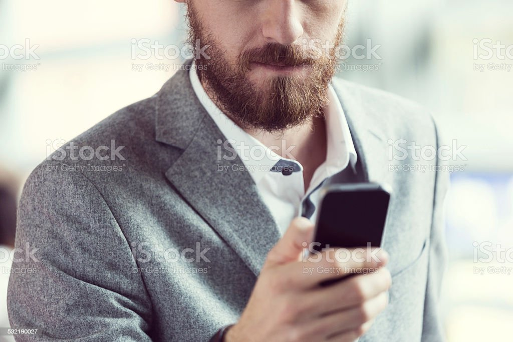 Bearded businessman using smart phone Close up of bearded businessman texting on smart phone. 2015 Stock Photo