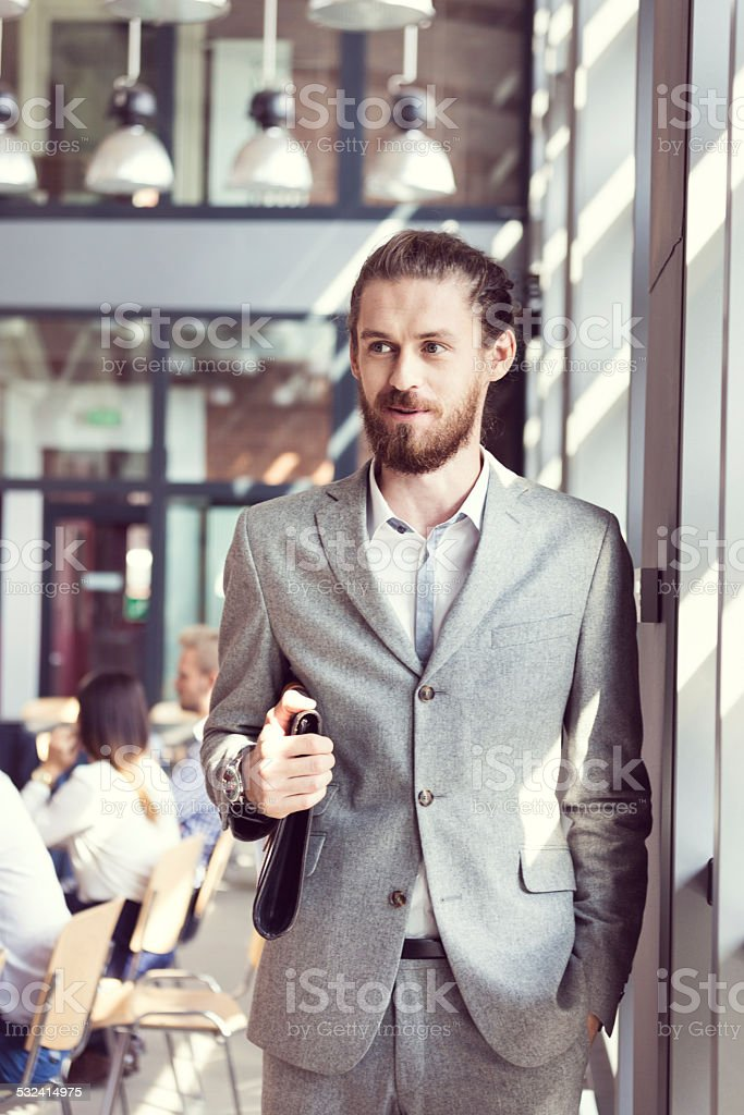 Bearded businessman wearing suit in the office Portrait of bearded businessman wearing grey suit and holding leather briefcase standing in the conference room. Coworkers sitting in the background. 2015 Stock Photo