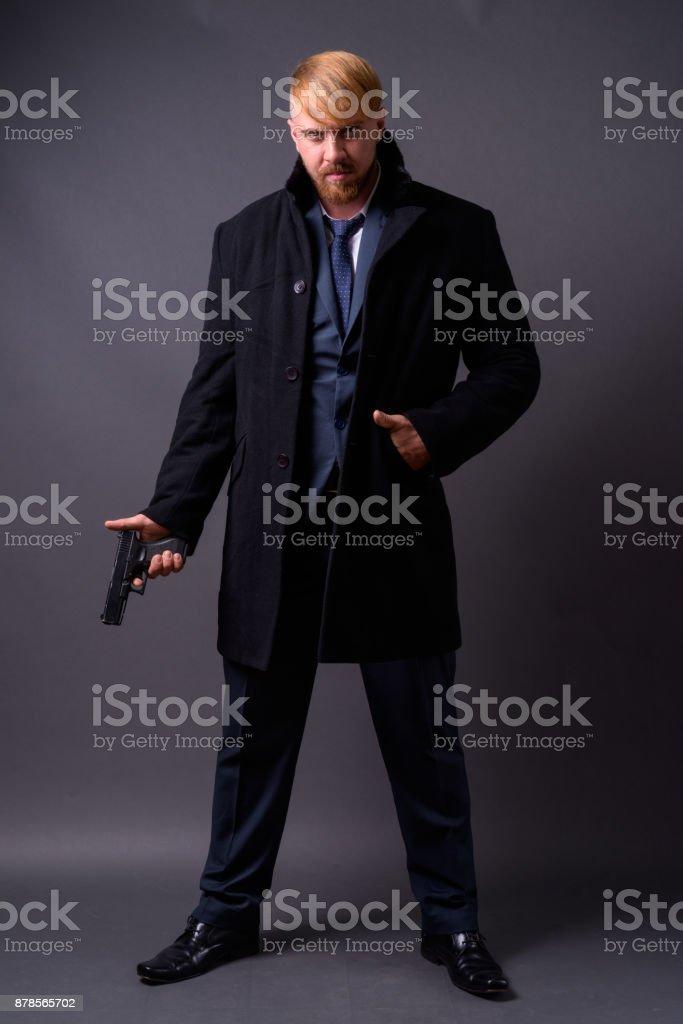 Bearded businessman with handgun against gray background stock photo
