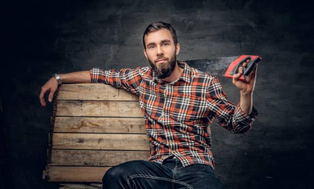 bärtige zimmermann männlich hält handsäge. - waldhandwerk stock-fotos und bilder