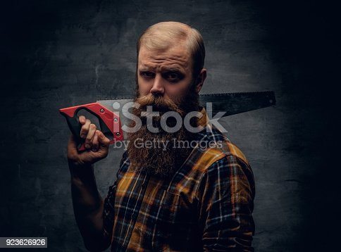 istock A bearded carpenter man dressed in a plaid shirt holds handsaw. 923626926