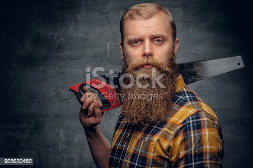istock A bearded carpenter man dressed in a plaid shirt holds handsaw. 923630482