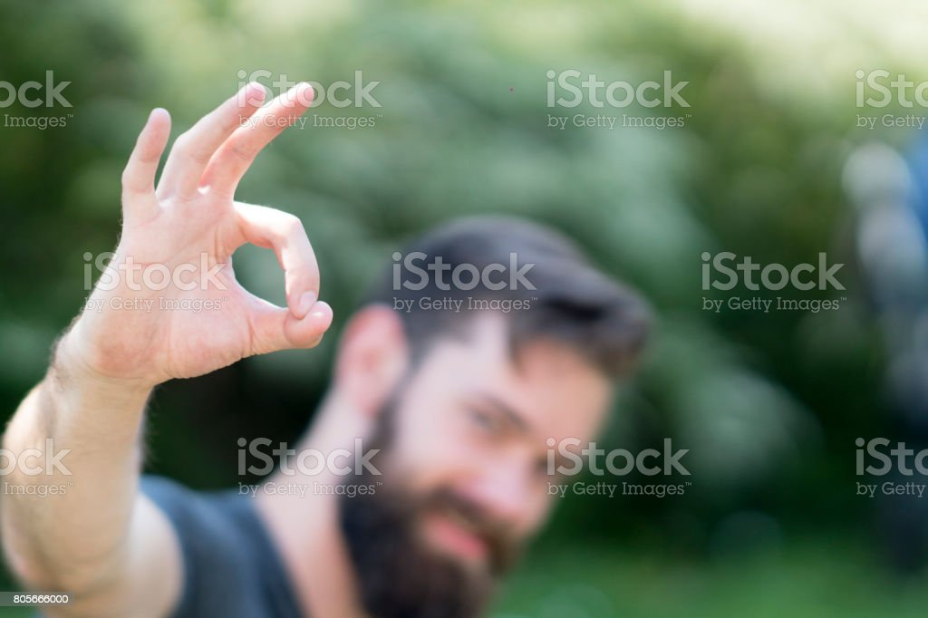 Bearded caucasian guy making ok sign at camera. Selective focus on foreground stock photo