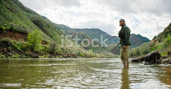 A Bearded Caucasian Man in His Twenties with a Backwards Baseball Cap and a PFD (Personal Floatation Device) Wades into the Colorado River in Western Colorado under an Overcast Sky