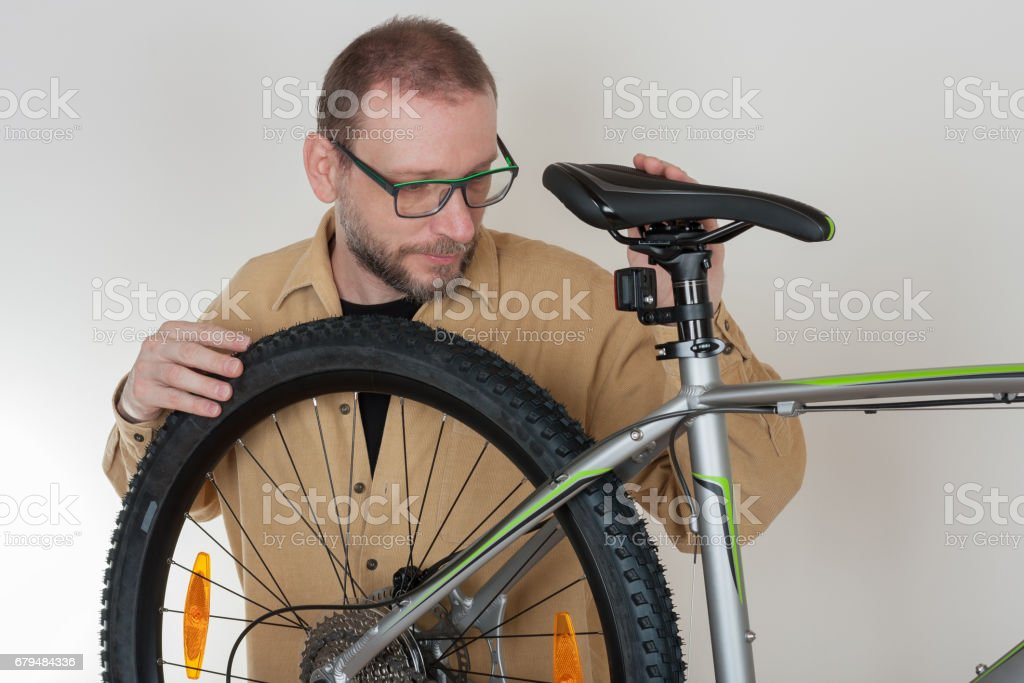 Bearded caucasian man repairing the mtb bicycle royalty-free stock photo