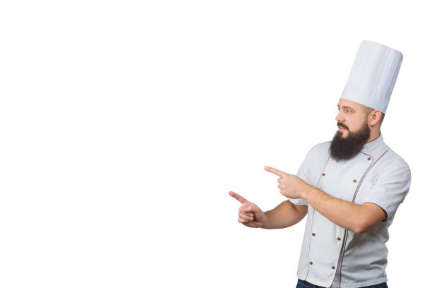 bearded chef cook pointing with his fingers isolated on white background, copy space on side. - kiss стоковые фото и изображения