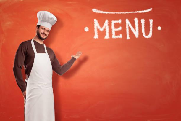 Un cocinero barbudo en uniforme blanco está parado y apunta a una indicación de menú grande tiza dibujado. - foto de stock