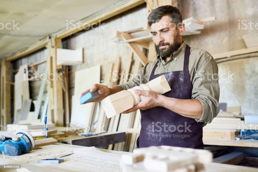 Bearded Craftsman Wrapped up in Work stock photo