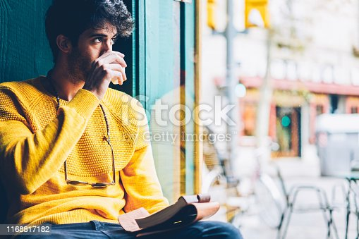 1174436608 istock photo Bearded creative young man drinking tasty coffee while looking out of window and thinking on new ideas for creating schedule.Thoughtful male dressed in casual yellow sweater enjoying beverage 1168817182