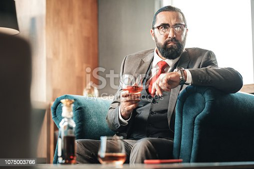 istock Bearded dark-haired lawyer drinking alcohol and smoking cigar 1075003766