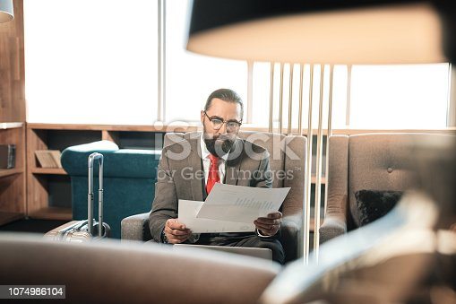 istock Bearded dark-haired mature businessman reading business contract 1074986104