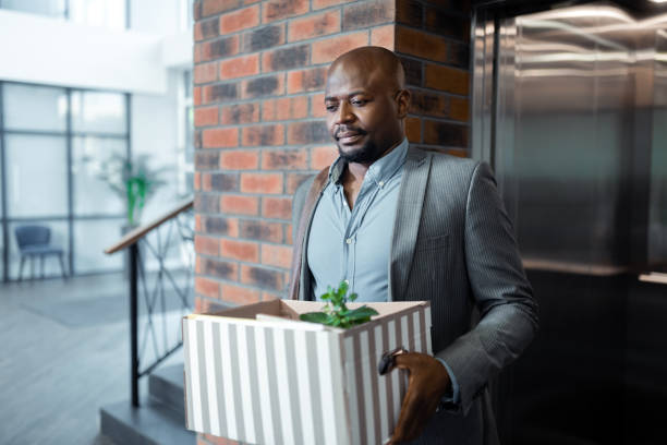 Bearded dark-skinned man leaving office holding box with plant inside Box with plant. Bearded dark-skinned man leaving office holding box with plant inside while standing near elevator downsizing unemployment stock pictures, royalty-free photos & images