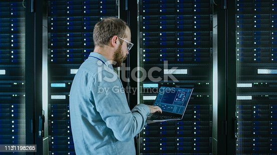1131208605 istock photo Bearded Data Center IT Engineer in Glasses is Walking Through Server Rack Corridor with a Laptop Computer. He is Visually Inspecting Working Server Cabinets. 1131198265