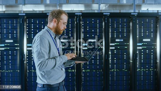 1131208605 istock photo Bearded Data Center IT Engineer in Glasses is Walking Through Server Rack Corridor with a Laptop Computer. He is Visually Inspecting Working Server Cabinets. 1131208605