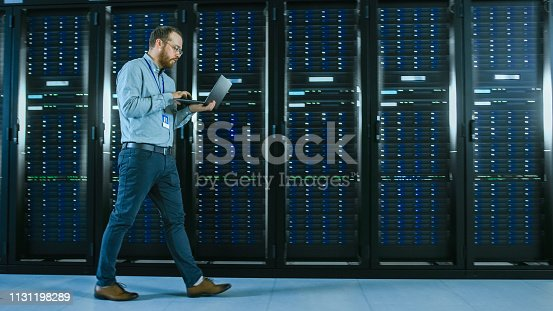 1131208605 istock photo Bearded Data Center IT Professional Walking Through Server Rack Corridor with a Laptop Computer. He Stops and Wirelessly Inspects Working Server Cabinets. 1131198289