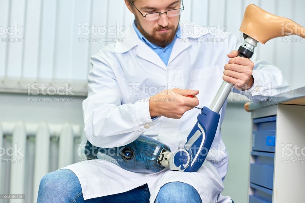 Bearded Doctor Assembling Prosthetic Leg stock photo