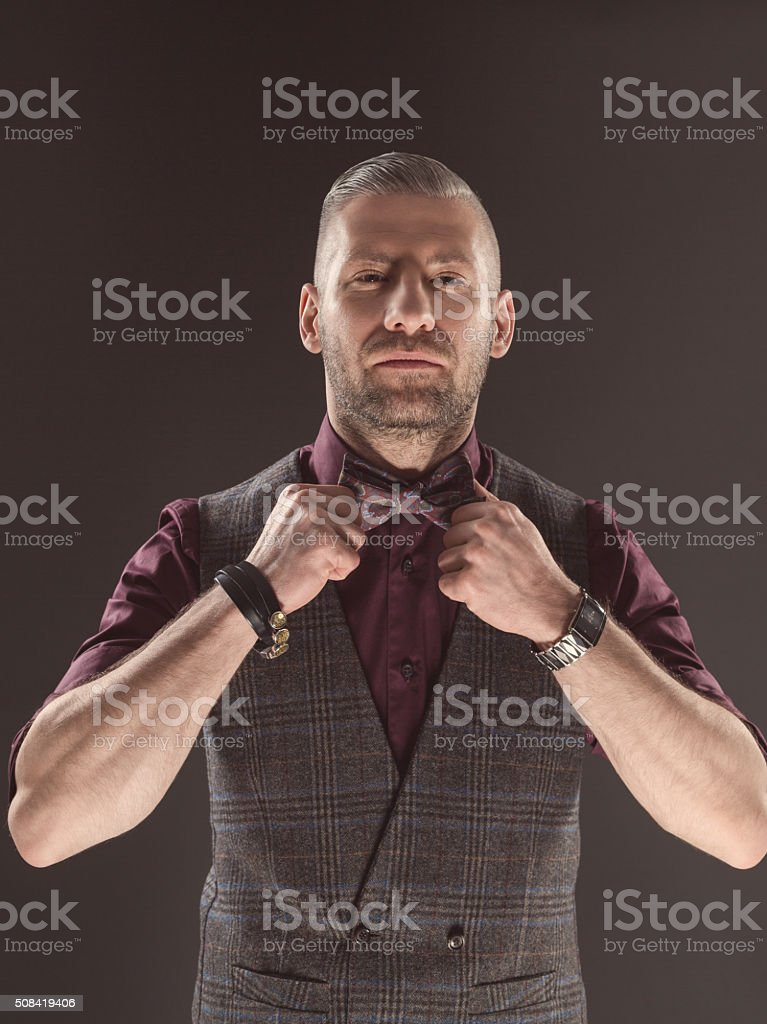 Bearded elegant man wearing bow tie and tweed vest Fashionable elegant bearded man wearing tweed vest, shirt and bow tie, looking at camera. Dark tone, black background. Adult Stock Photo