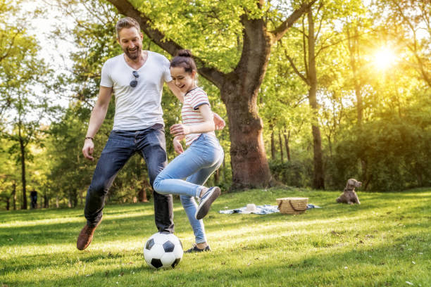 bearded father and teenage daughter playing soccer on summer meadow leisure, family, outdoor, weekend, teenager, parent, father, dog, relaxing, nature, leisure equipment stock pictures, royalty-free photos & images