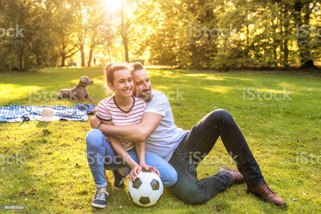 bärtige Vater umarmen Teenager-Tochter im park Lizenzfreies stock-foto
