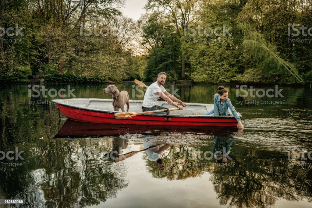 bearded father sculling row boat with teenage daughter and dog - foto stock