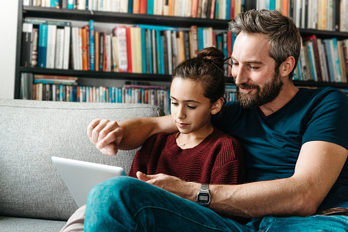 Bearded Father With Daughter Tapping At Digital Tablet On Couch Stock Photo - Download Image Now