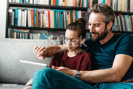 Bearded Father With Daughter Tapping At Digital Tablet On Couch Stock Photo & More Pictures of 12-13 Years
