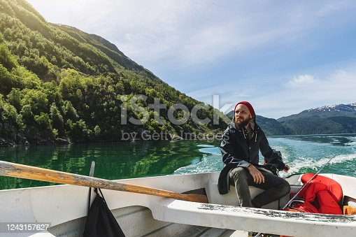Fisherman on a small fishing boat: sailing in a fjord in Norway